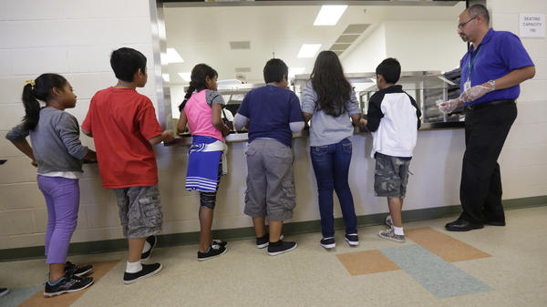 Detained immigrant children line up in the cafeteria at the Karnes County Residential Center, in Texas.