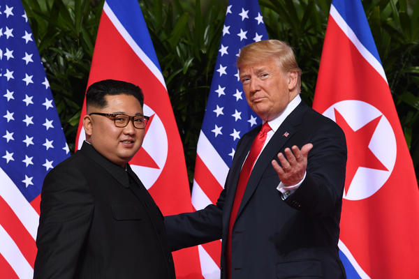 President Trump gestures to reporters as he meets with North Korea's leader Kim Jong Un at the start of the U.S.-North Korea summit in Singapore on Tuesday.