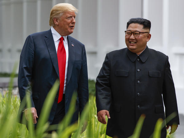 President Trump and Kim Jong Un stroll after lunch on Tuesday.
