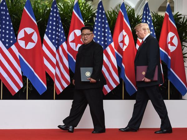 President Trump and North Korean leader Kim Jong Un carry their documents after the signing ceremony at the end of their summit.