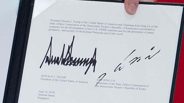 The signatures of President Donald Trump and North Korean leader Kim Jong Un are seen on a document held up by Trump following a signing ceremony during their U.S.-North Korea summit in Singapore Tuesday.