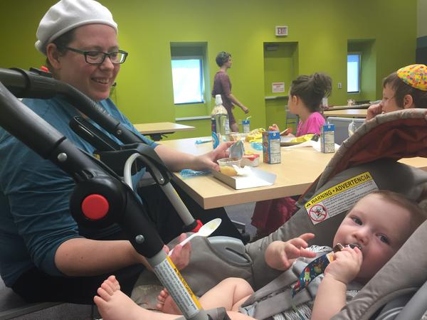 Elizabeth Quinn feeds Eliyahu Mazer applesauce at the Johnson County Central Resource Library on Monday.