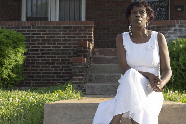 Simone Townsend, 52, sits on the stoop of her Penrose home. She says she sees an increase in crime during the summer months in her neighborhood.
