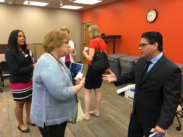 Mario San Bartolome (right) of Molina Healthcare talks with a representative from Attorney General Mike DeWine's office.