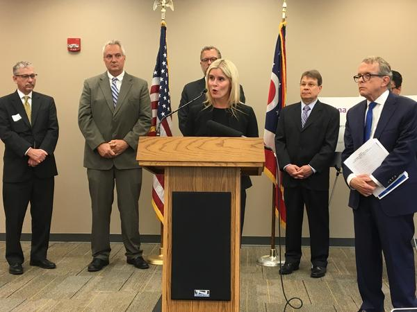 Miranda Motter, president and CEO of the Ohio Association of Health Plans, speaks at a press conference with health insurers and AG Mike DeWine (to her right).