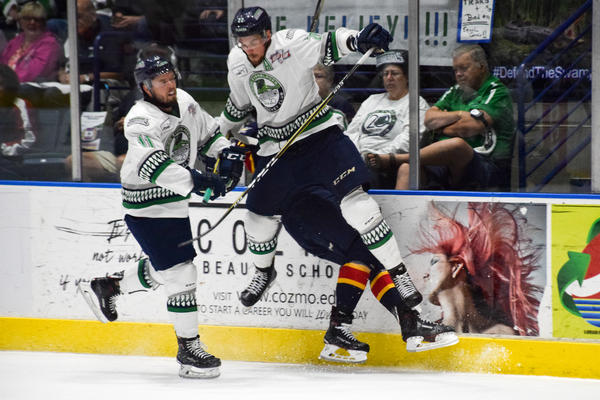 Everblades defenseman Clark Seymour leaps into the air to check an Eagles player against the boards.