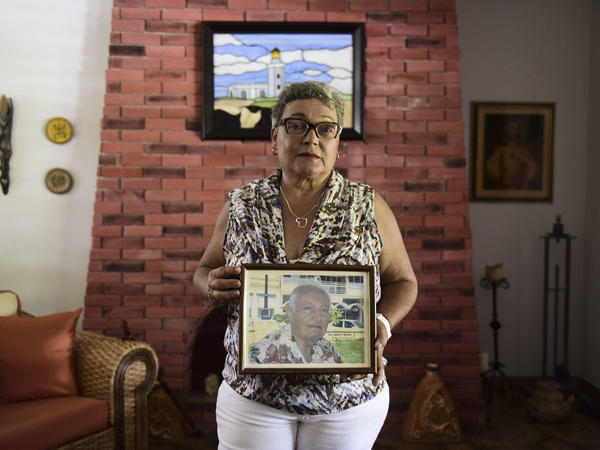 Puerto Rican Nerybelle Perez poses with a portrait of her father, World War II veteran Efrain Perez, who died after his ambulance was turned away from the island's largest public hospital when it had no electricity or water following  Hurricane Maria.