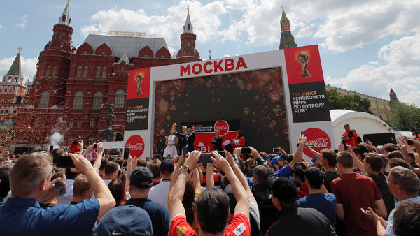 People watch as the FIFA World Cup trophy is displayed in central Moscow. Russia is hosting soccer's mega-event for the next month — and people around the world will be watching matches live, online and on TV.