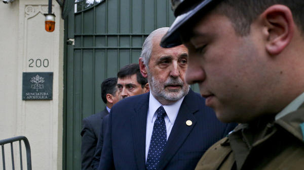 Chile's National Prosecutor Jorge Abbott, center, leaves the Apostolic Nunciature after meeting with Archbishop Charles Scicluna in Santiago, Chile. Police raided Roman Catholic Church offices in two Chilean cities Wednesday looking for files related to a long-running sex abuse scandal.