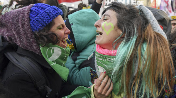 Abortion rights activists break out into happy tears in Buenos Aires, reveling with other demonstrators at the bill's passage Thursday.