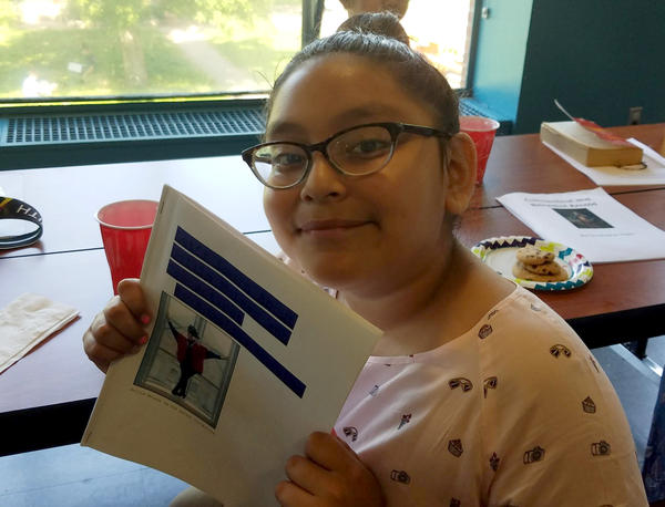 Angelina Morales holds her Connecticut history chapter book; Chapter 2 is about the African-American dancer, Dollie McLean.