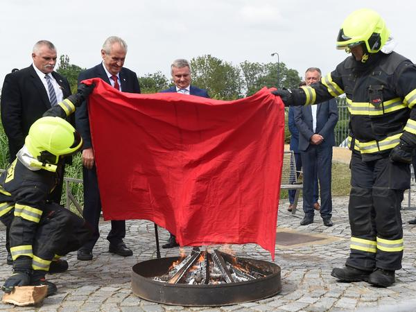 Czech President Milos Zeman (back row, second from left) looks on with glee Thursday as firefighters burn a large piece of red textile representing the red underwear his political opponents have used to mock him.
