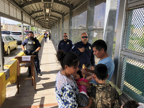 The Berduo family speaks with authorities as they try to cross the international bridge between Matamoros, Mexico, and Brownsville, Texas.