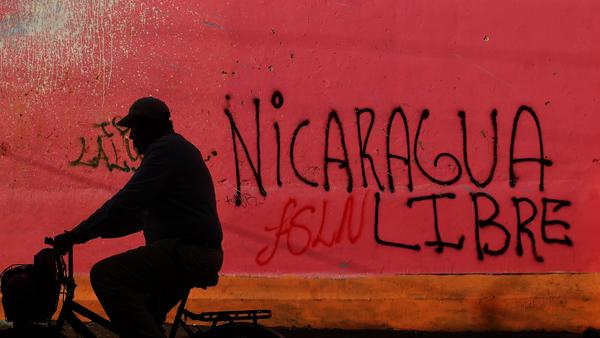 A cyclist rides by the graffitied headquarters of President Daniel Ortega's Sandinista National Liberation Front, which protesters occupied and looted Thursday.