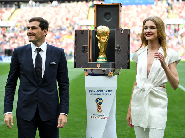 Former Spain footballer Iker Casillas and model Natalia Vodianova next to the World Cup and its custom Louis Vuitton case.