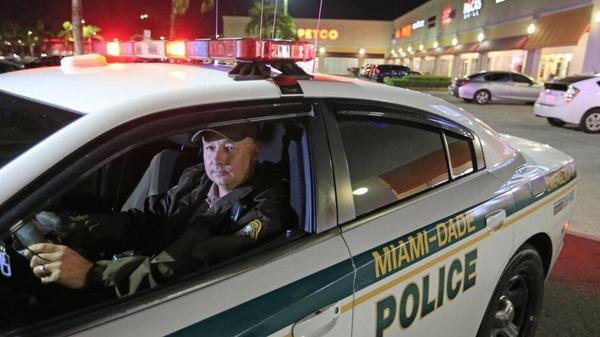 Miami Dade Police Officer Kenny Bonnet patrols in Kendall late last year. County police officers might be assigned to school campuses starting in August.