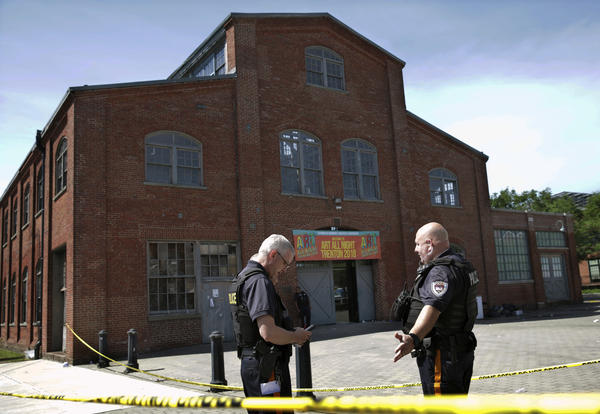 Police stand guard outside the historic Roebling Wire Works building where a shooting resulted in numerous injuries and at least one death during the Art All Night festival in Trenton, N.J.
