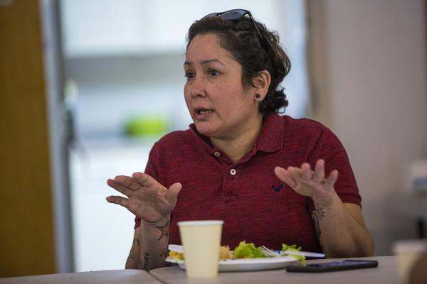 Dagamer Rivera talks with other evacuees about their housing situations. (Jesse Costa/WBUR)