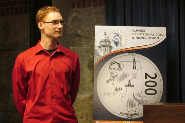Hayden Schumer stands before his winning design while addressing reporters at a press conference in Springfield.