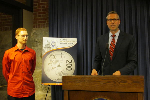 Illinois Treasure Mike Frerichs announces the winning coin face while its designer, Hayden Schumer, looks on.