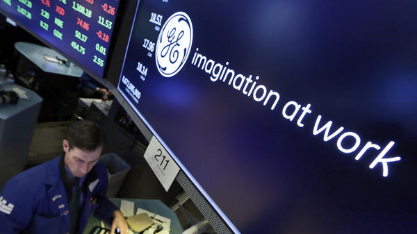 Specialist John McNierney works at the post that handles General Electric on the floor of the New York Stock Exchange in January. The struggling company is being dropped from the Dow Jones industrial average.
