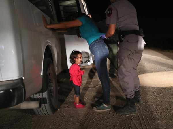 A 2-year-old from Honduras cries as her mother is searched and detained near the U.S.-Mexico border on June 12 in McAllen, Texas.
