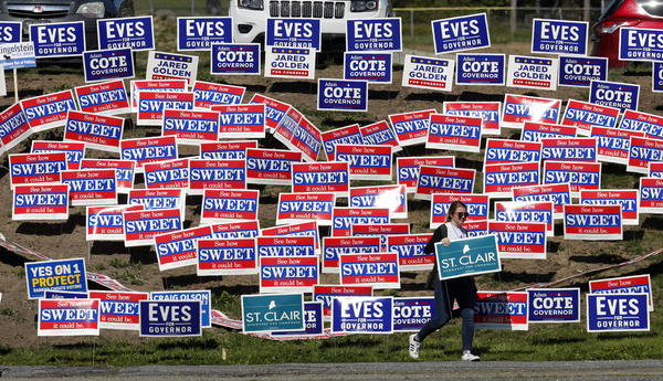 Jacqueline Morris of Bangor, Maine, looks for a spot to plant a sign for 2nd District Congressional candidate Lucas St. Clair outside the Colisee at the Democratic Convention, Friday, May 18, 2018, in Lewiston, Maine.