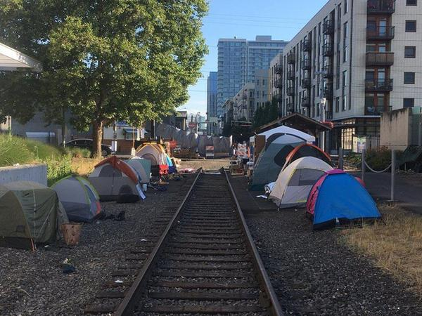 <p>Tents line trolley tracks outside the ICE facility in Southwest Portland, Wednesday, June 20, 2018.</p>