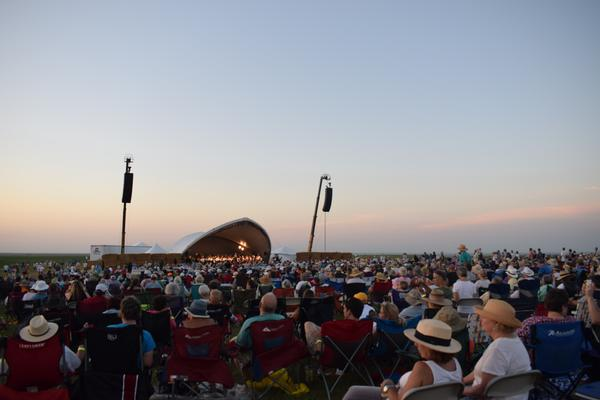 The crowd of Symphony guests watch the concert as the sun sets over the prairie. About 7,000 people attend the event each year.