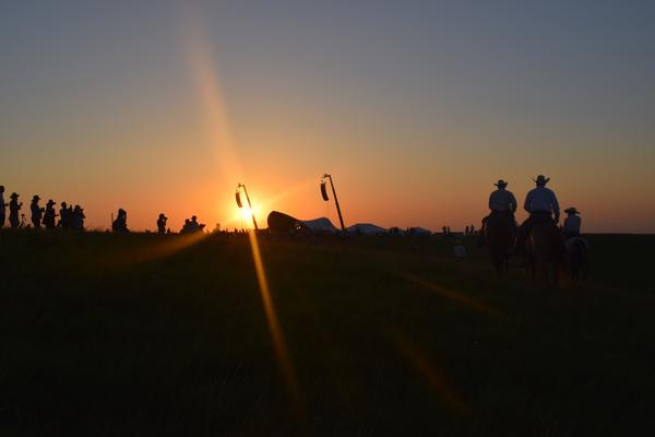 The sun sets on the prairie as volunteers on horseback ride in for the evening. The riders guard the outskirts of the site during the concert and play an important role in keeping the event safe.