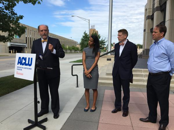 Mark Johnson, (left) attorney for ACLU of Kansas, speaks to reporters outside the Robert J. Dole Federal Courthouse on Tuesday. (Left to right) Lauren Bonds and Micah Kubic represent the ACLU of Kansas, and Scott Moore (right) is a registered voter.