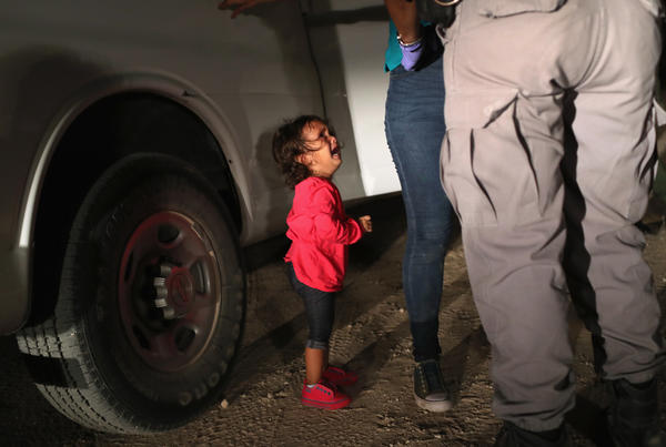 A 2-year-old Honduran girl cries as an official searches her mother in McAllen, Texas, near the U.S.-Mexico border, earlier this month. For many, the image has become indelibly associated with a Trump administration policy that for weeks separated migrant children from their parents — but the girl's father says she was not separated from her mother.