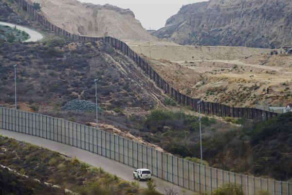 A border patrol car drives past the old border wall just east of Borderfield State Park where construction is set to begin on approximately 14.5 miles of new fencing on June 4 in San Ysidro, Calif.