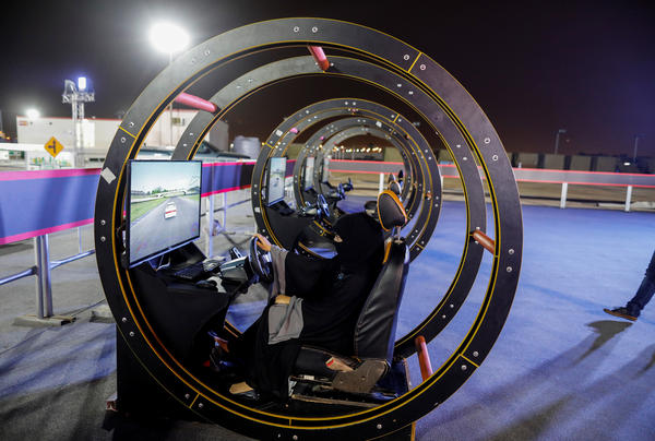 A Saudi woman sits in a driving simulator during an awareness campaign in Jeddah on June 21.