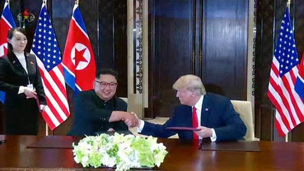 In this image made from video released by KRT on June 14, 2018, shows North Korean leader Kim Jong Un smiling at the media as he shakes hands with U.S. President Donald Trump during a summit in Singapore, June 12, 2018.