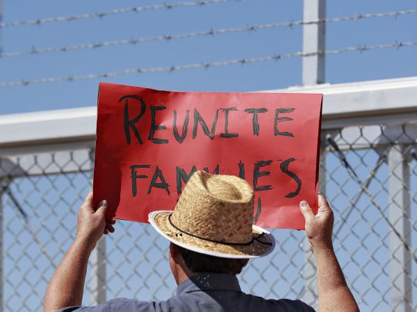 A protester holds a sign outside a closed gate at the Port of Entry facility, last week in Fabens, Texas, where tent shelters are being used to house separated family members.