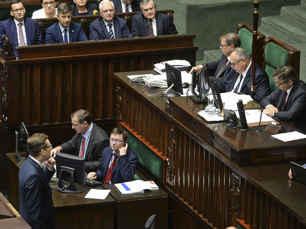 Polish lawmakers voted overwhelmingly to remove prison penalties in a controversial Holocaust law. Prime Minister Mateusz Morawiecki (upper left) looks on as a right-wing lawmaker blocks the podium in a failed effort to obstruct the vote.