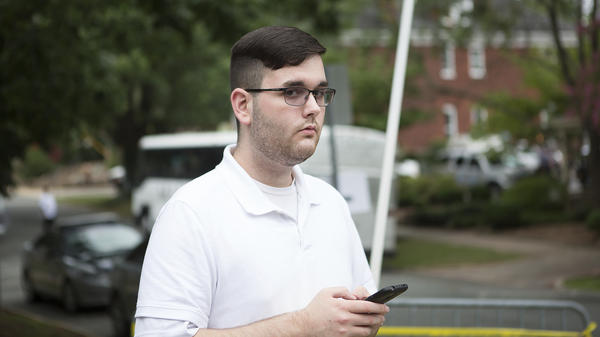 James Alex Fields Jr. stands on the sidewalk ahead of a rally in Charlottesville, Va., on Aug. 12, 2017. Later that day he is accused on ramming his car into a crowd of counterprotesters, killing Heather Heyer. On Wednesday he was charged with federal hate crimes.