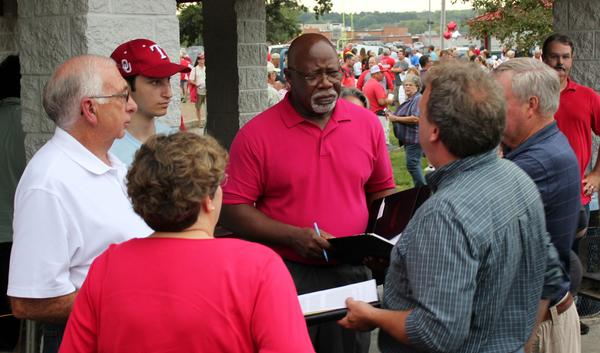 Rep. Willie Dove (center, in red) talking with Rep. Jim Karelskint (left, in white) and other organizers of a public meeting about the Tyson project last year.