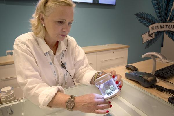 Sira Naturals' Lynne Rutkowski examines a marijuana sample at the company's Needham dispensary. (Robin Lubbock/WBUR)