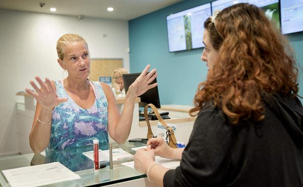 Karlene Kadra, a registered nurse, talks with Sira Naturals' Malari Martin about the products available at the dispensary. (Robin Lubbock/WBUR)