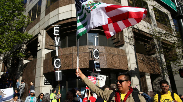 A former top attorney at ICE in Washington state has pleaded guilty to stealing the personal information of immigrants who were at risk of deportation and using the data to defraud banks. Here, protesters stand outside the ICE office in Seattle during a demonstration in May.
