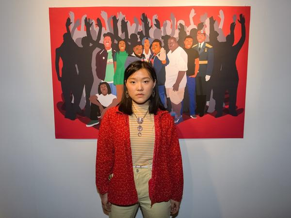 Ameya Okamoto, 18, poses in front of her work.