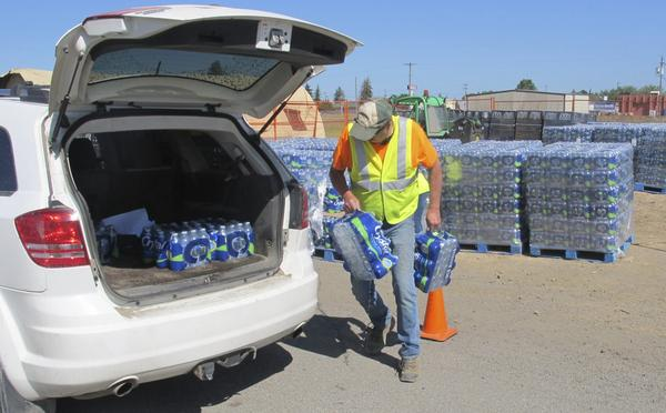 In this photo taken June 5, 2017, a U.S. Air Force worker loads bottled water into a vehicle in Airway Heights, Wash. Tests near Fairchild Air Force Base found groundwater tainted with two industrial chemicals used for years in firefighting foam and consumer products such as nonstick cookware. (Nicholas K. Geranios/AP)