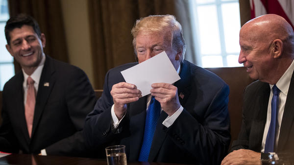 "President Trump kisses a mock-up of a 1040 ""postcard"" during a meeting with GOP congressional leaders."
