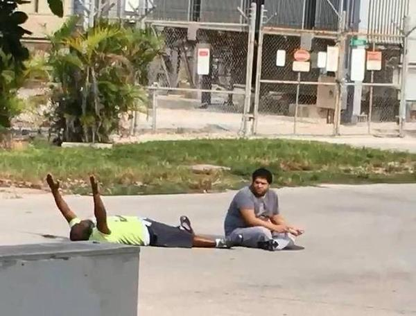 Behavioral therapist Charles Kinsey lies on the ground with his hands raised while Arnaldo Rios, an autistic man, ignores police orders. Kinsey, who was caring for the man, was shot in the leg by North Miami police officer Jonathan Aledda.