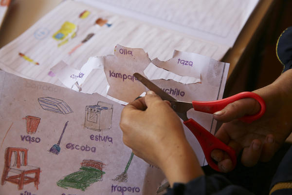 A student cuts out vocabulary words and pictures for a project.