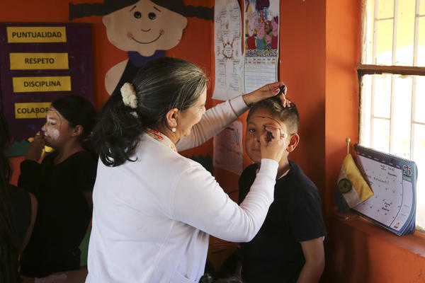 Teacher Maria Isabel Camango Guido paints mime makeup on one of her students for a performance.