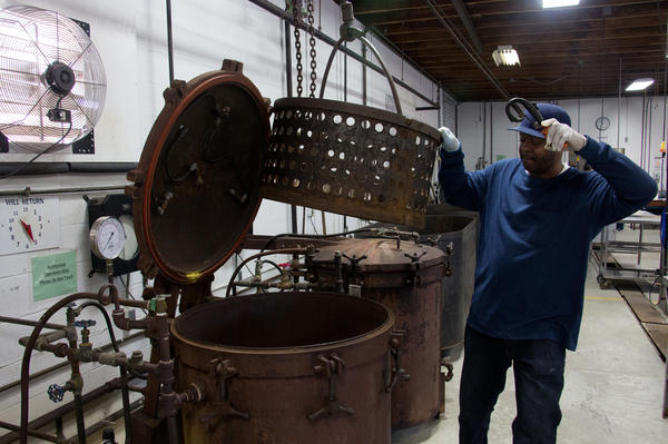 Rodney Scott, who works at the public cannery, loads a batch of cans into one of the two giant pressure cookers in the cannery.