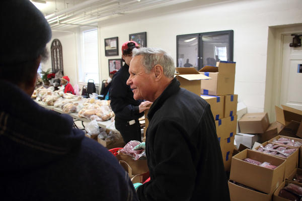Phil Ferlazzo, a volunteer with Empowering Culpeper, distributes free venison to people who need it. Boxes of frozen venison are stacked on pallets behind him.